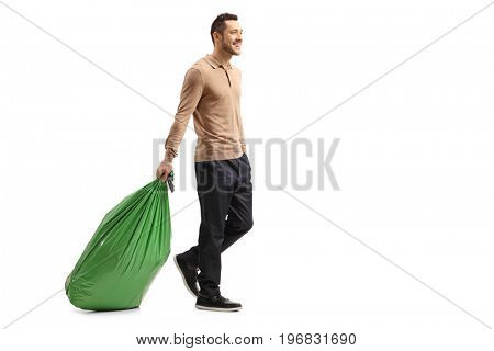 Full length profile shot of a guy dragging a garbage bag isolated on white background