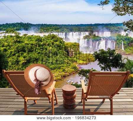 Incredible exotic waterfalls of Iguazu in South America. Two wooden chaise lounges face waterfalls. On one hangs an straw female hat. Concept of exotic and eco-tourism