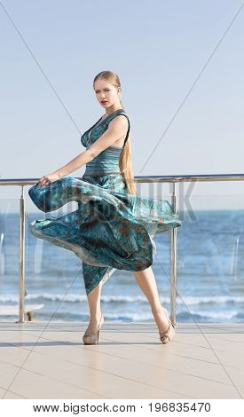 An attractive young female in a long silk emerald dress on a light blue sky background. Beautiful girl in a stylish dress on a glass balcony. A concept of femininity, peace and harmony.