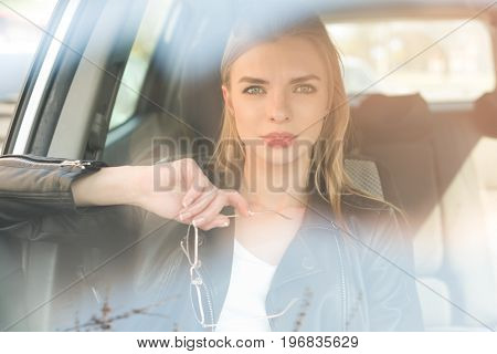 Portrait Of Beautiful Blond Woman With Sunglasses In Hand Sitting In Car