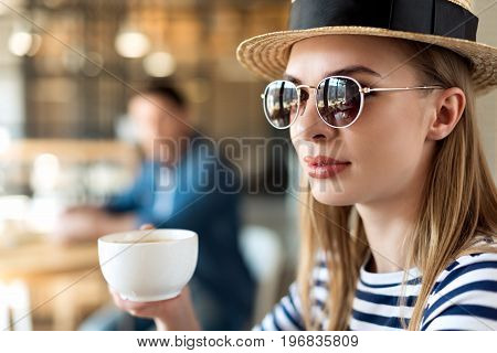 Portrait Of Stylish Woman In Hat And Sunglasses Holding Cup Of Coffee In Cafe