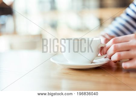 cropped shot of female hands holding cup of coffee on saucer