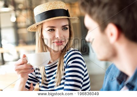 Portrait Of Woman With Cup Of Coffee In Hand Looking At Man While Sitting In Cafe