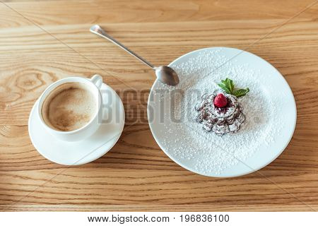 Top View Of Cup Of Coffee And Sweet Dessert On Wooden Table In Cafe