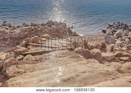 Natural stairway to the stone shore covered with salt at the Dead Sea coast Jordan.
