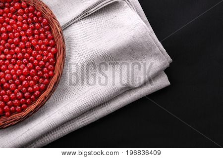 Delicious red currant in a brown wooden basket on a saturated black background. Sour and bright red currant on a gray burlap sack. Organic and nutritious berries for summer juices.