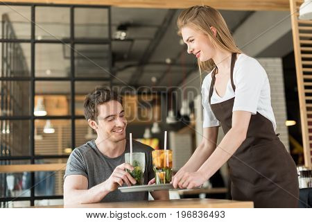 Smiling Waitress In Apron Bringing Order To Client In Cafe