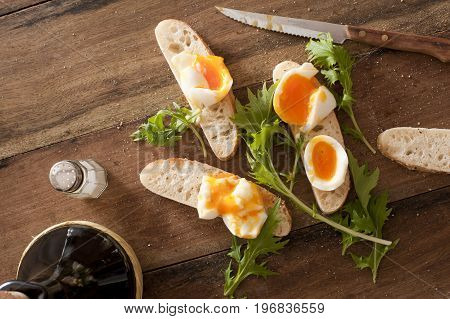 Bread soldiers with soft-boiled eggs thin strips of toasts with greens and knife over wooden table