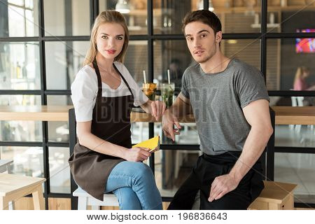 Portrait Of Young Waiter And Waitress Looking At Camera In Cafe