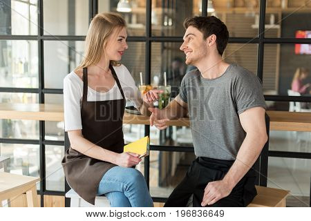 Young Waiter And Waitress Having Conversation During Break At Work In Cafe