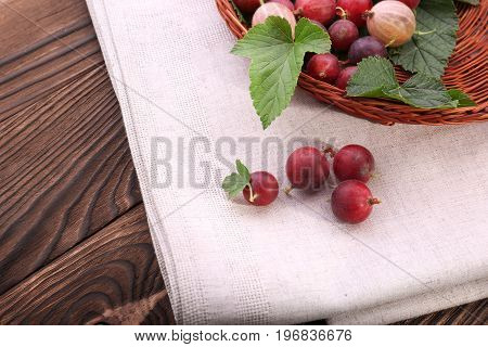 A view from above of colorful gooseberries on a light gray cloth on a wooden background. Rustic and healthful gooseberries with fresh green leaves in a wicker brown basket.