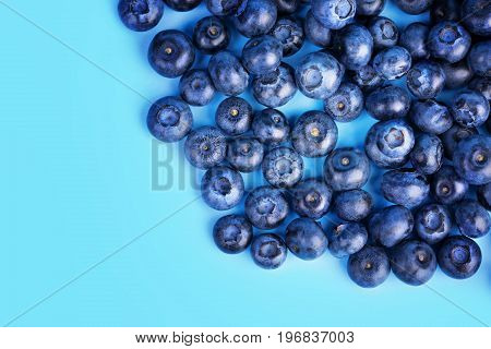 A view from above on a pile of tasteful blueberries on a saturated blue background.  A close-up of refreshing and appetizing blueberries. Healthful ingredients for sweet summer fruit salads.