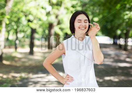 A joyful and feminine student on a green sunny park background. An expressive young lady with a stylish short haircut is laughing. A happy and casual girl posing and touching her face.