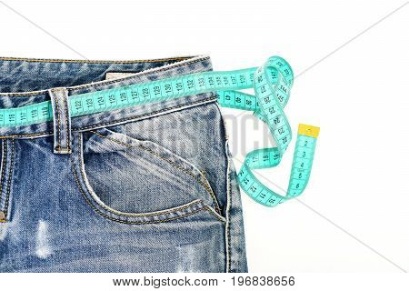 Blue jeans with blue measure tape instead of belt. Healthy lifestyle and dieting concept. Close up of jeans with measure tape around waist. Upper part of denim trousers isolated on white background.