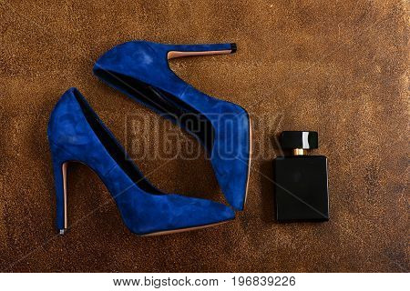 Female Shoes On Textured Brown Background. Fashion And Scent Concept.