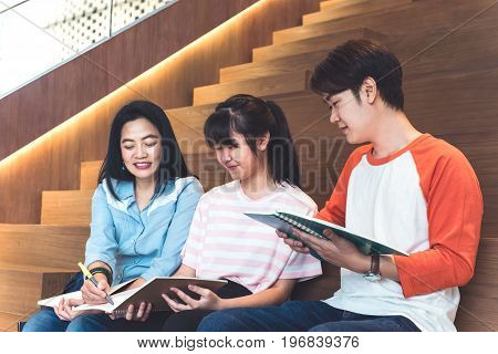 Groups of asian teenage students studying together at university stair library.