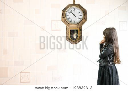 Pretty child girl in a beautiful black dress looking at a big yellow wall clock and counting and thinking about time ages and growing