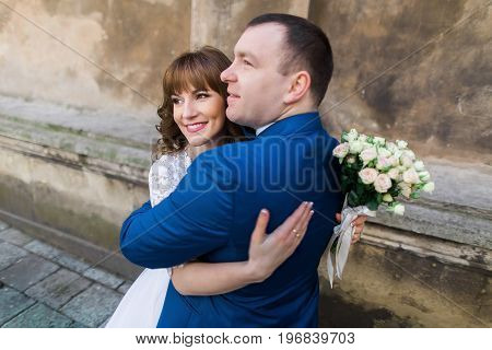 Happy hugging newlyweds in the street. Close-up portrait