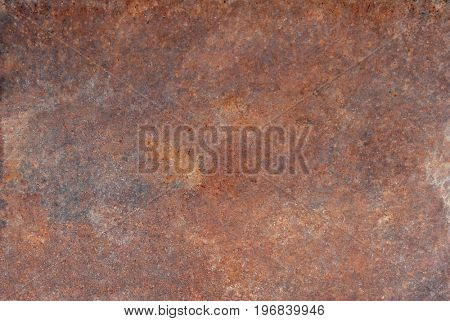 Brown old rusted corroded metal or steel sheet horizontal wall background as abstract dirty textured metallic vintage industrial closeup for retro grungy surface design. A rough iron aged plate