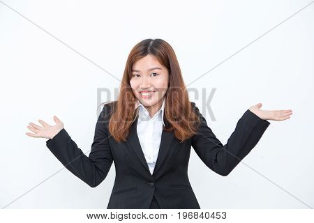 Closeup portrait of smiling Asian business woman looking at camera, shrugging and spreading hands. Isolated view on white background.