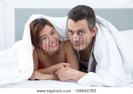 Smiling young couple lying in bed. They are covered with blanket. Man is looking at camera. Front view.