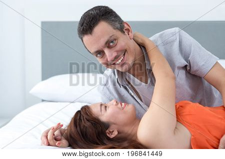 Young Asian woman embracing husband. They are lying in bed. Man is looking at camera. Side view.