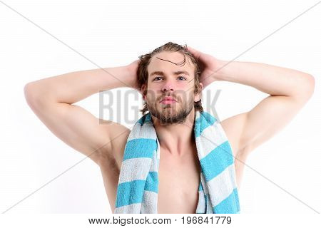 Macho with striped blue towel around neck and big muscles isolated on white background. Man with naked torso confident face beard and wet hair stretching his muscles. Shower time and sports concept