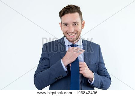 Cheerful young male entrepreneur preparing for important meeting. Positive handsome man with stubble tying tie in morning while getting dressed. Wearing suit concept