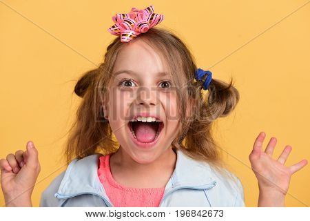Girl with happy smiling face isolated on warm yellow background. Kid with cute pink bow on head and messy hair. Holiday and present concept. School girl and paper bow for present boxes