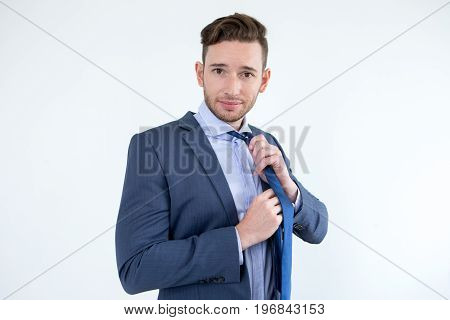Handsome businessman taking off necktie and looking at camera. He tired from work and routine. He standing opposite white background and adjusting tie. Business lifestyle concept