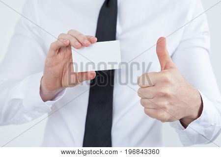 Close-up of male consultant showing business card and thumb-up. Successful advisor presenting himself as highly qualified specialist. Good choice concept