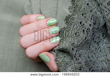 Beautiful female hand with green nail art with gold mica.
