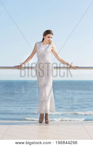 Full-length photo of a romantic female in a long white dress. The tall pretty young lady relaxing on a sunny glass balcony on a saturated blue sea background. Elegance, beauty, fashion concept.