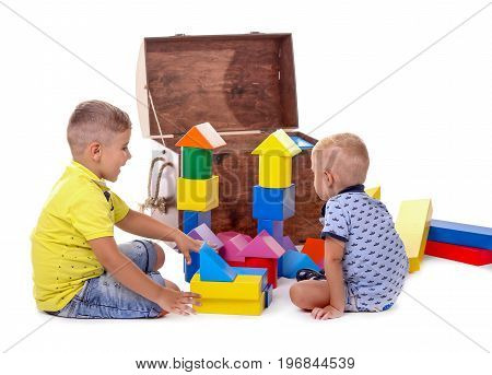 Two cute little boys play with colorful cubes, isolated on white background. An open brown wooden box with creativity toys. Multicolored toys for children.