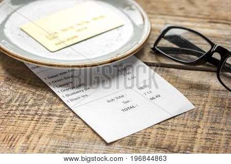 restaurant bill paying by credit card and glasses on wooden table background