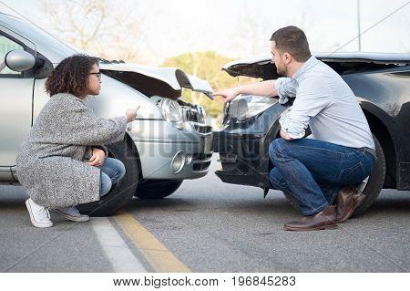 Man and woman arguing after bad car crash