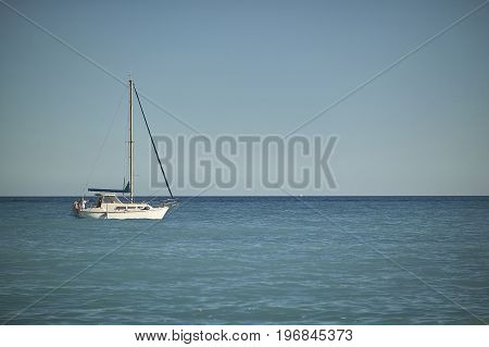 Beautiful sailing boat while sailing in the sea near the coast ready to dock.