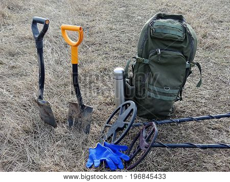 Shovels and metal detectors on dry grass