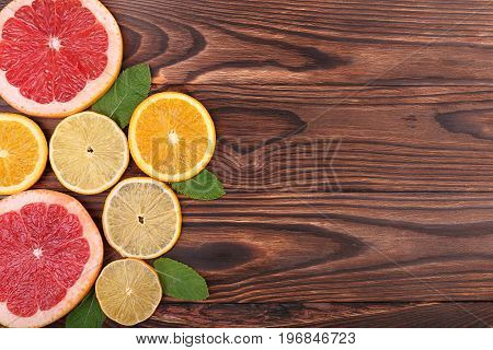 Close-up of juicy, fresh and ripe citrus fruits with leaves on a wooden background. Fresh slices of exotic and sour lemon, sweet orange and juicy grapefruit with green leaves of mint, top view.
