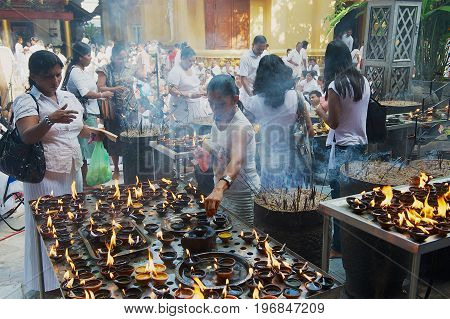 COLOMBO, SRI LANKA - MAY 17, 2011: Unidentified people light candles at the Buddhist temple during Vesak religious celebration in Colombo, Sri Lanka.
