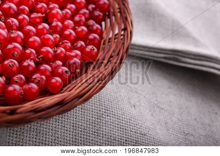Macro colorful red berries on a gray background. Juicy, fresh tasteful red currant in a wooden basket. A spacious crate with berries on a light piece of fabric. Fruit ingredient.