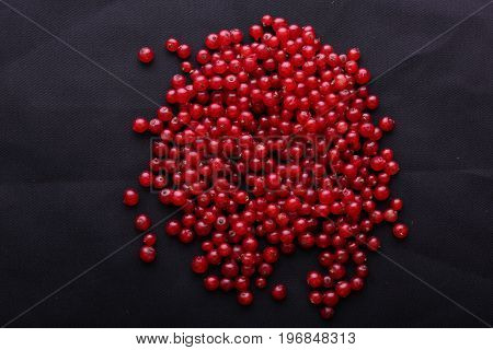 Close-up of a bright red currant on a black background. The heap of tasteful and healthful red currant for vegetarian breakfast. Fresh juicy berries.