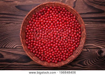 A composition of juicy berries on a bright brown background. Fresh red currant in a crate. A basket full of delicious currant. The eco-friendly wooden basket on a table with fresh currant.