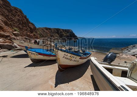 Aljezur Portugal - July 6 2017: Traditional fishing boats at the small fishing port of Portinho do Forno in Aljezur Portugal