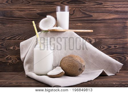 Fresh and organic products from coconuts. Tropical nut milk in a mason jar and a glass and whole and cut coconuts with leaves and a spoon with coco chips on a fabric and on a dark wooden background.