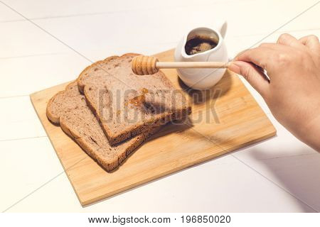 Close-up of slice of toast bread with honey on wood table