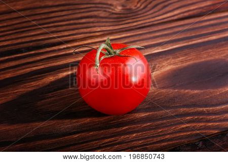 A single bright red tomato on a dark brown wooden background. Close-up of ripe vegetables. Delicious summer vegetables full of useful vitamins. Freshness, organic, natural, juicy concept.