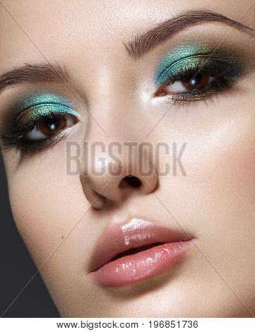 Beautiful young model with fashion make up, perfect skin. Trendy colorful smoky eyes. Green smoky eyes