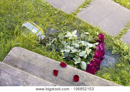 A glass jar with bouquet of beautiful roses tipped over near a wooden stairs outdoor image concept of relationships.