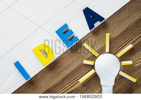 Lightbulb and idea word on the wooden background. Colorful word IDEA on two color wooden background. The concept of creativity.